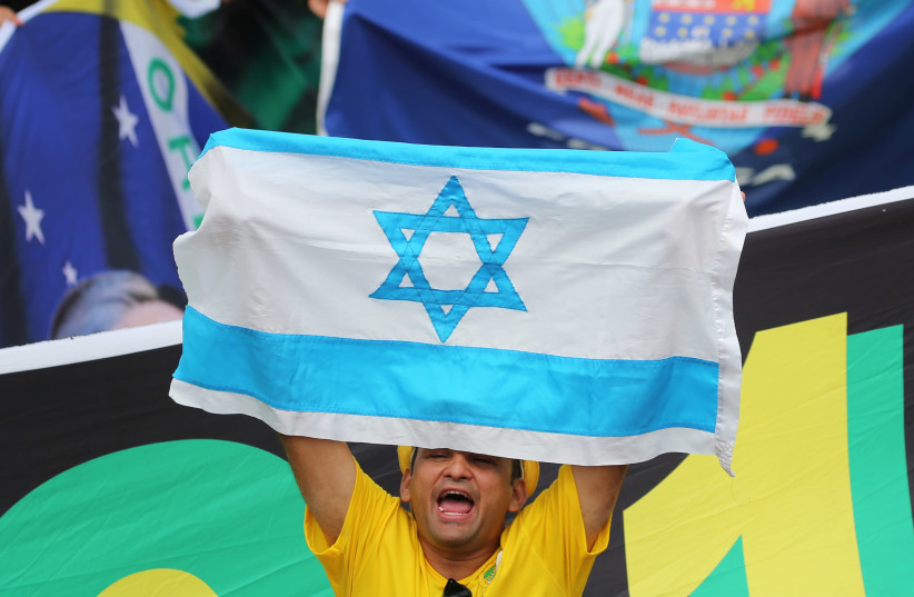 A man displays national flag of Israel as supporters of Brazil's new President Jair Bolsonaro gather outside the Planalto Palace ahead of Bolsonaro's swear-in ceremony, in Brasilia, Brazil, January 1, 2019.  (photo credit: SERGIO MORAES / REUTERS)