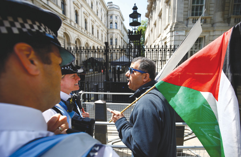 POLICE OFFICERS speak to a demonstrator holding a Palestinian flag in London ahead of Prime Minister Benjamin Netanyahu's visit in June.  (photo credit: REUTERS)