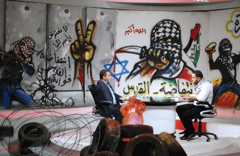 PALESTINIAN PRESENTER Raji Al-Hams (right) listens to Hamas official Salah al-Bardweel at the studio of Hamas-run al-Aqsa TV in Gaza City in 2015. The studio is decorated with slogans praising the 'Knife Intifada.' (photo credit: REUTERS)