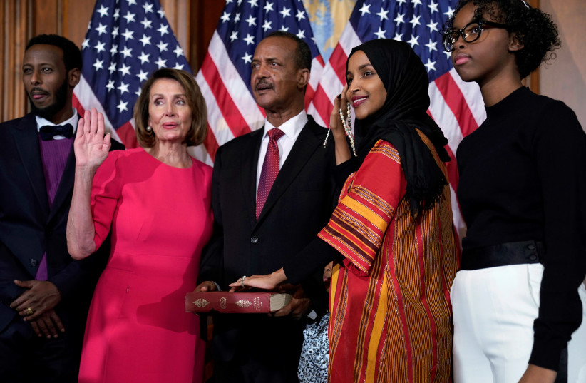 Rep. Ilhan Omar (D-MN) poses with Speaker of the House Nancy Pelosi (D-CA) for a ceremonial ceremonial swearing in picture on Capitol Hill in Washington, U.S., January 3, 2019 (photo credit: JOSHUA ROBERTS / REUTERS)