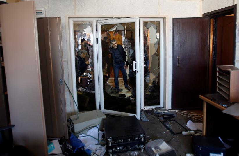 Palestinians inspect the damage inside the office of Palestine TV, in Gaza City January 4, 2019 (photo credit: AHMED ZAKOT / REUTERS)