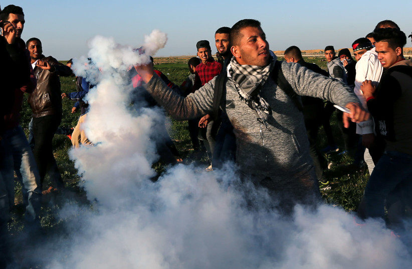 A Palestinian demonstrator returns a tear gas canister fired by Israeli troops during a protest at the Israel-Gaza border fence, in the southern Gaza Strip January 4,2019 (photo credit: IBRAHEEM ABU MUSTAFA / REUTERS)