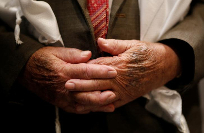 The hands of Shalom Shtamberg, a 93-year old Holocaust survivor, are seen during his bar mitzvah ceremony, a Jewish coming-of-age celebration traditionally marked by boys at the age of 13, in Haifa, Israel August 31, 2017 (photo credit: AMIR COHEN/REUTERS)