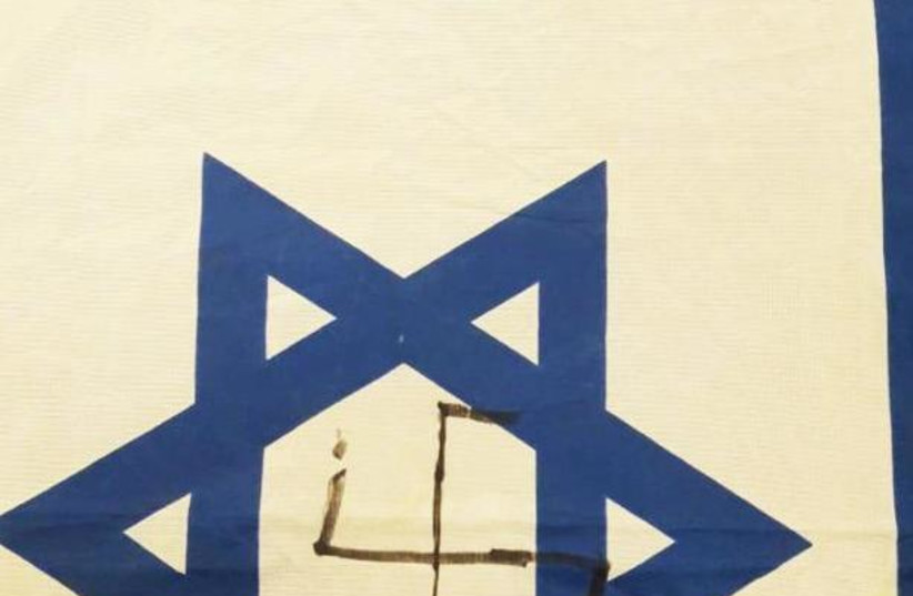 """A defaced Israeli flag with the Nazi Swastika and a Hebrew caption saying """"Death to Zionists.""""   (photo credit: Courtesy)"""