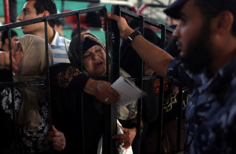 A woman gestures as she waits to travel into Egypt through Rafah border crossing after it was opened by Egyptian authorities for humanitarian cases, in the southern Gaza Strip. (photo credit: REUTERS/IBRAHEEM ABU MUSTAFA)