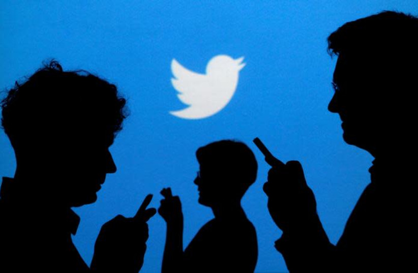 People holding mobile phones are silhouetted against a backdrop projected with the Twitter logo in this illustration picture taken September 27, 2013. (photo credit: REUTERS/KACPER PEMPEL)