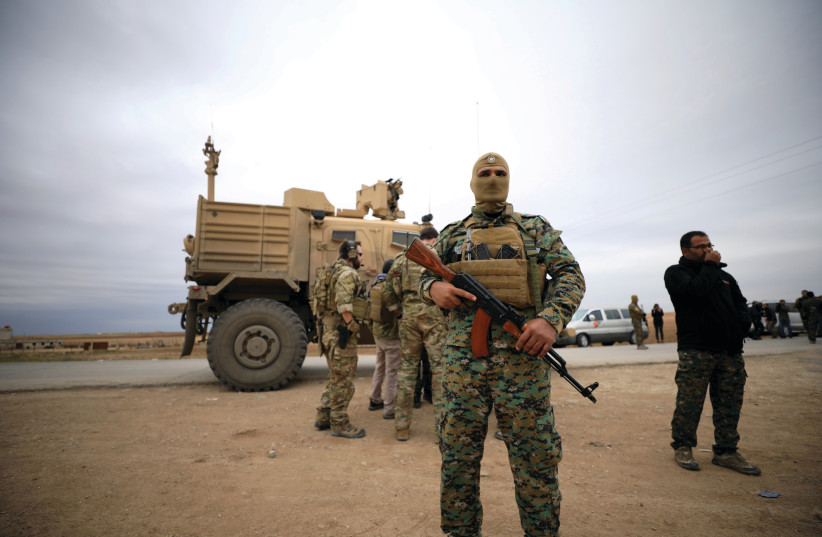 SYRIAN DEMOCRATIC FORCES and US troops are seen during a patrol near Turkish border in Hasakah, Syria, in November. (photo credit: RODI SAID / REUTERS)