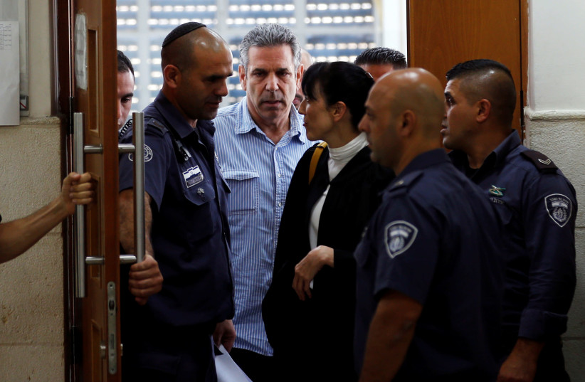 Gonen Segev, a former Israeli cabinet minister indicted on suspicion of spying for Iran, is escorted by prison guards as he leaves the court in Jerusalem, July 5, 2018 (photo credit: RONEN ZVULUN/REUTERS)