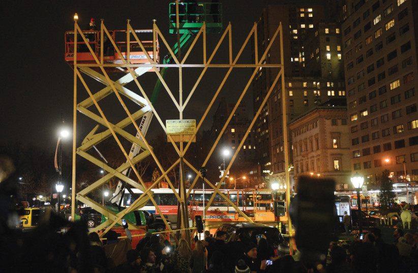 A RABBI lights the 'World's Largest Menorah' in Manhattan in 2017. (photo credit: ANDREW SAVULICH/TNS)
