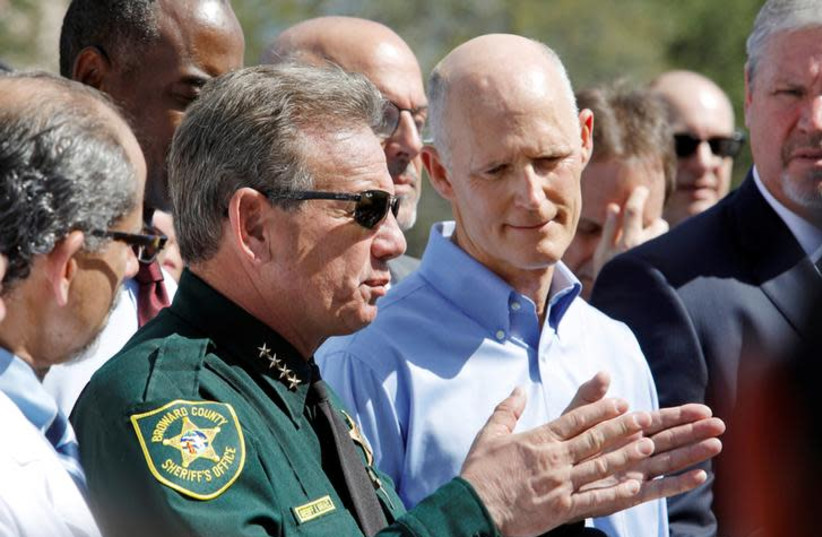 Broward County Sheriff Scott Israel speaks to the media while Florida Governor Rick Scott listens outside Marjory Stoneman Douglas High School one day after a shooting at the school left 17 dead, in Parkland, Florida, U.S. (photo credit: JONATHAN DRAKE / REUTERS)