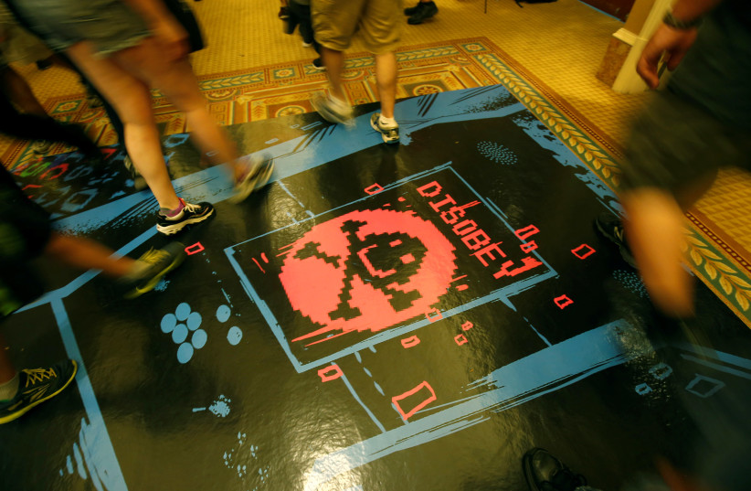 People walk past a floor graphic during the Def Con hacker convention in Las Vegas, Nevada, U.S. on July 29, 2017. (photo credit: STEVE MARCUS/REUTERS)