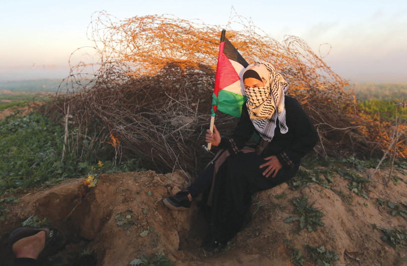 A PALESTINIAN woman takes cover during a protest at the Israel-Gaza border fence on Friday (photo credit: REUTERS/IBRAHEEM ABU MUSTAFA)