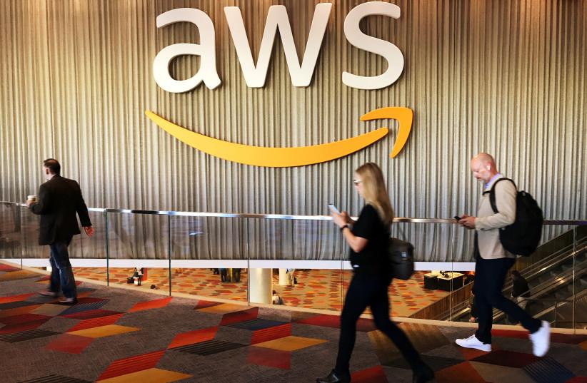 Attendees at Amazon.com Inc annual cloud computing conference walk past the Amazon Web Services logo in Las Vegas, Nevada, U.S., November 30, 2017.  (photo credit: SALVADOR RODRIGUEZ / REUTERS)