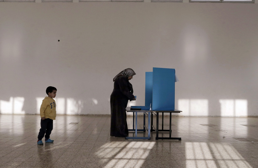 An Israeli Arab stands behind a voting booth before casting her ballot at a polling station in the northern town of Umm el-Fahm March 17, 2015. Millions of Israelis turned out to vote on Tuesday in a tightly-fought election, with Prime Minister Benjamin Netanyahu facing an uphill battle to defeat a  (photo credit: AMMAR AWAD / REUTERS)