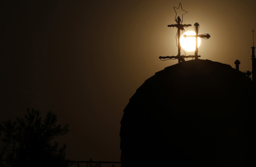 A Roman Catholic church cross is seen as the sun sets before Christians take part in a candlelight march and prayed for peace in Gaza, Jordan, and in the Arab region, in Al-Fuheis city, near Amman, August 11, 2014. Participants passed by three churches, the Roman Catholic, Greek Orthodox and Latin C (photo credit: REUTERS/MUHAMMAD HAMED)