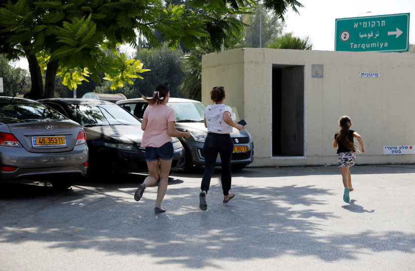 Israelis run for shelter as a siren sounds during a rocket attack near Yad Mordechai at the Israeli side of the Israel Gaza border July 14, 2018  (photo credit: AMIR COHEN/REUTERS)