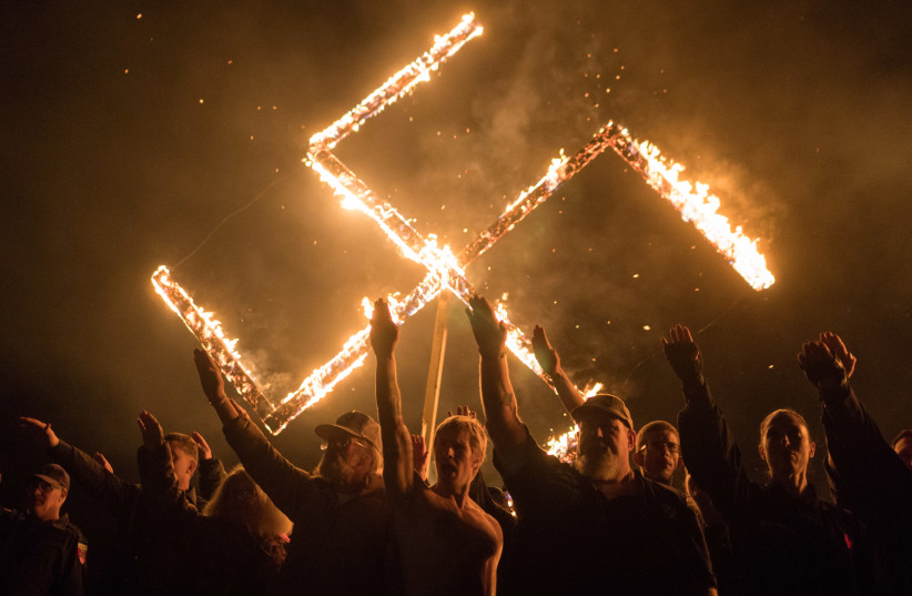 Supporters of the National Socialist Movement, a white nationalist political group, give Nazi salutes while taking part in a swastika burning at an undisclosed location in Georgia, US on April 21, 2018 (photo credit: GO NAKAMURA/REUTERS)