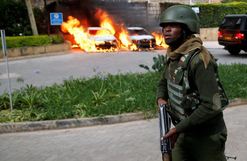 A policeman runs past burning cars at the scene where explosions and gunshots were heard at the Dusit hotel compound, in Nairobi, Kenya (photo credit: REUTERS/BAZ RATNER)
