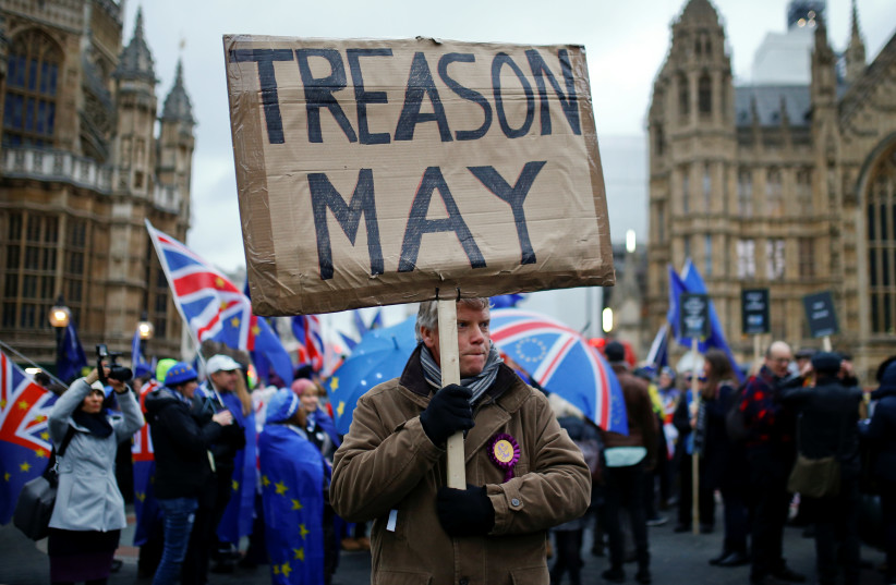 A pro-Brexit protester holds a banner as anti-Brexit protesters demonstrate outside the Houses of Parliament, ahead of a vote on Prime Minister Theresa May's Brexit deal, in London, Britain, January 15, 2019. (photo credit: REUTERS/HENRY NICHOLLS)
