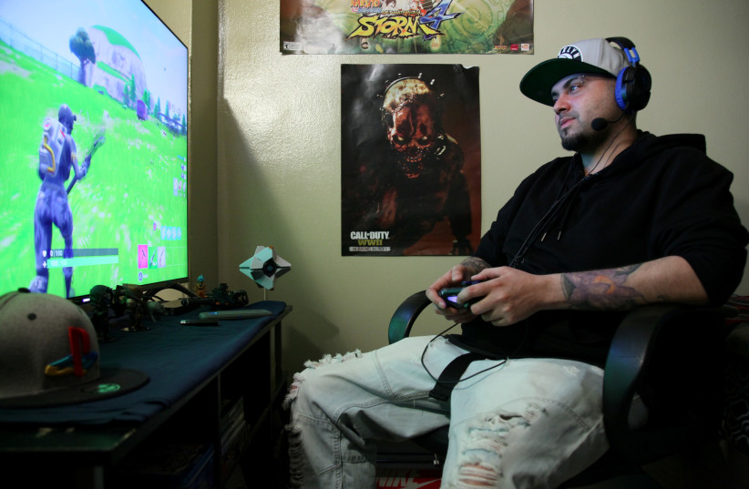 Twenty Seven-year-old Christian Acevedo plays the video game 'Fortnite Battle Royale' from his home in Brooklyn, New York, U.S., on April 21, 2018. Acevedo says if he doesn't have to work the next day, he often stays up all night to play the popular game (photo credit: JILLIAN KITCHENER/REUTERS)