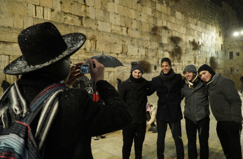 An orthodox Jew takes pictures of tourists at the Western Wall (photo credit: MARC ISRAEL SELLEM)