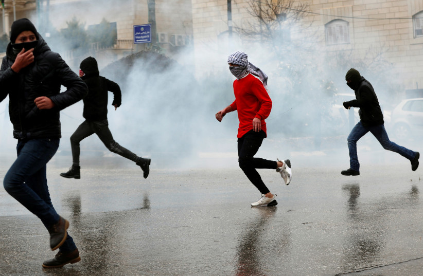 Palestinians run from Israeli forces in Ramallah, January 9, 2019 (photo credit: MOHAMAD TOROKMAN/REUTERS)