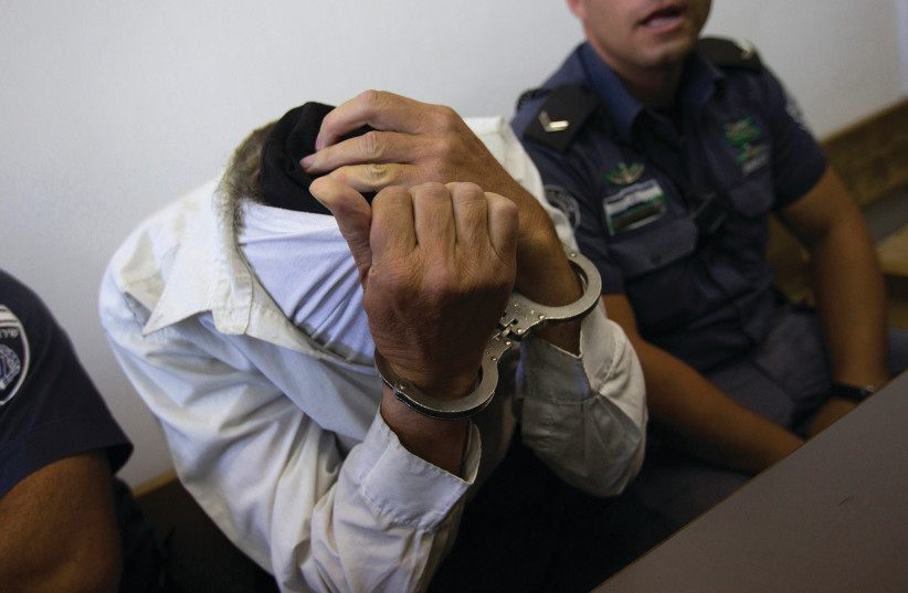 A SUSPECT IN a Jerusalem court. Can the Shin Bet's motto – that it goes after all terrorism equally – be disproven?  (photo credit: RONEN ZVULUN/REUTERS)
