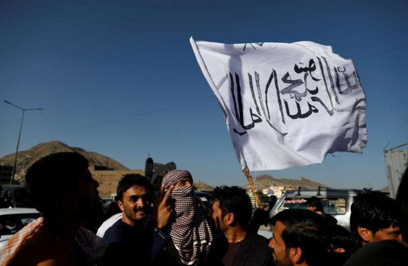 A member of the Taliban holds a flag in Kabul, Afghanistan June 16, 2018. The writing on the flag reads: 'There is no god but Allah, Muhammad is the messenger of Allah' (photo credit: REUTERS/MOHAMMAD ISMAIL)