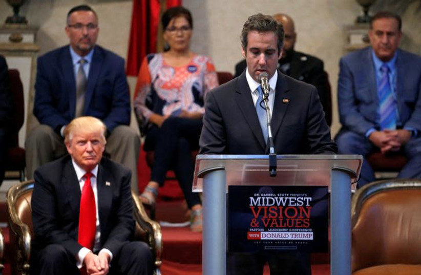 President Donald Trump listens as his former personal attorney Michael Cohen delivers remarks on his behalf (photo credit: REUTERS/JONATHAN ERNST)