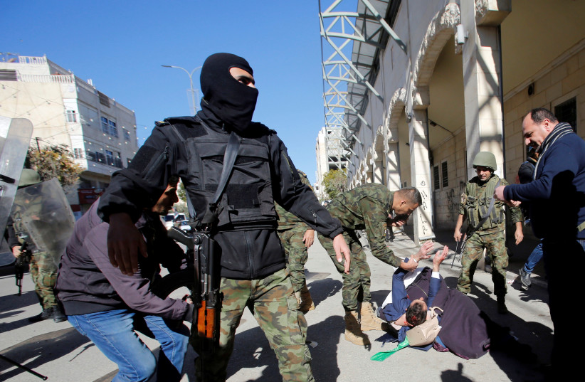 A woman and a wounded protester fall on the ground as members of Palestinian security forces disperse a Hamas demonstration in the Palestinian Authority controlled side of Hebron, December 14, 2018 (photo credit: MUSSA QAWASMA / REUTERS)
