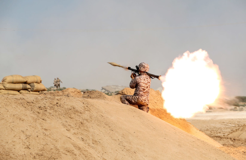 A member of military units of the IRGC Ground Force fires a rocket launcher as they launched war games in the Gulf, December 22, 2018 (photo credit: HAMED MALEKPOUR/TASNIM NEWS AGENCY VIA REUTERS)