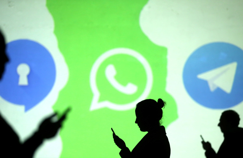 Silhouettes of mobile users next to the Whatsapp logo, March 28, 2018. (photo credit: REUTERS/ DADO RUVIC)
