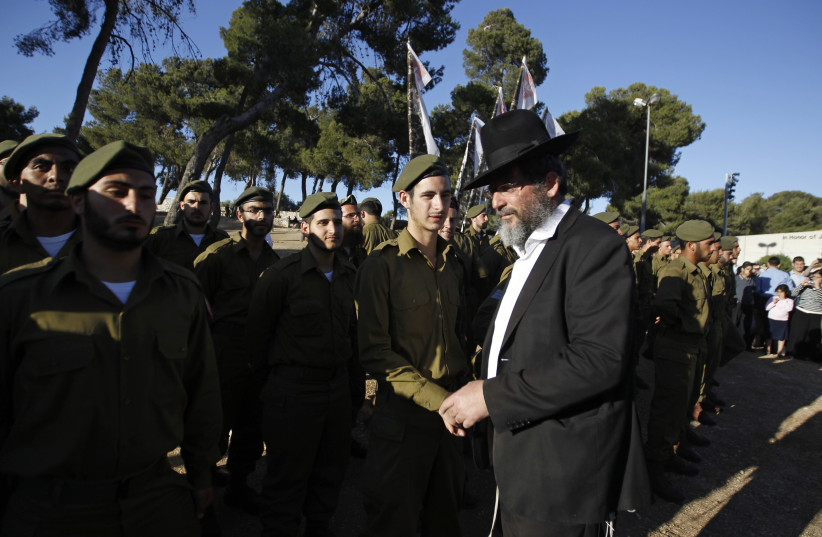 An ultra-Orthodox, or Haredi, Jewish man walks past Israeli soldiers of the Netzah Yehuda Haredi infantry battalion during their swearing-in ceremony in Jerusalem (photo credit: AMMAR AWAD/REUTERS)