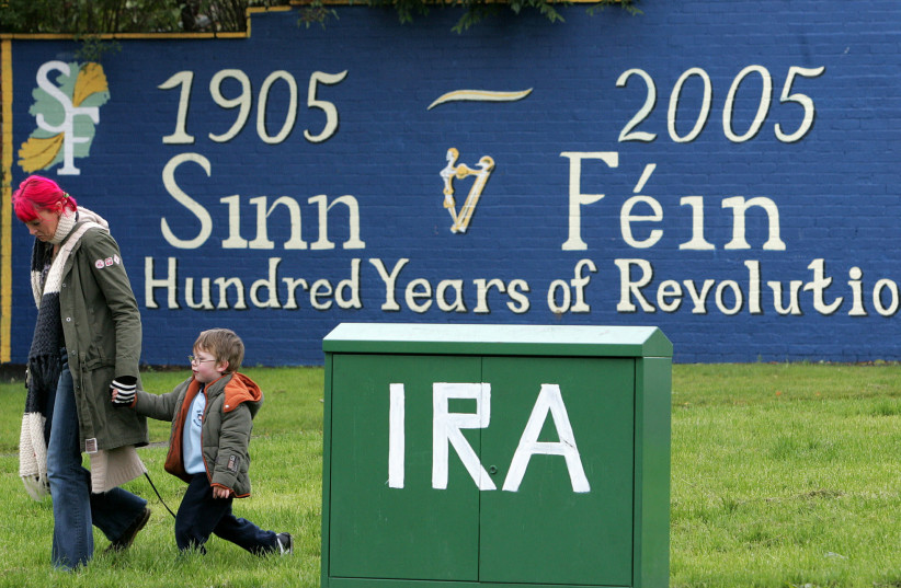 A file photograph, dated October 22, 2004, shows a mother and child walking past a new republican mural in west Belfast (photo credit: REUTERS)