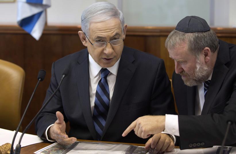 Israel's Prime Minister Benjamin Netanyahu speaks with Cabinet Secretary Avichai Mandelblit (R) during the weekly cabinet meeting in Jerusalem (photo credit: MENAHEM KAHANA / REUTERS)