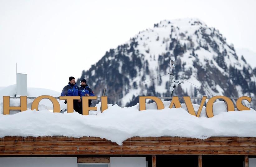 Policemen keep watch ahead of inauguration of World Economic Forum in Davos, Switzerland, 2019. (photo credit: REUTERS/ARND WIEGMANN)