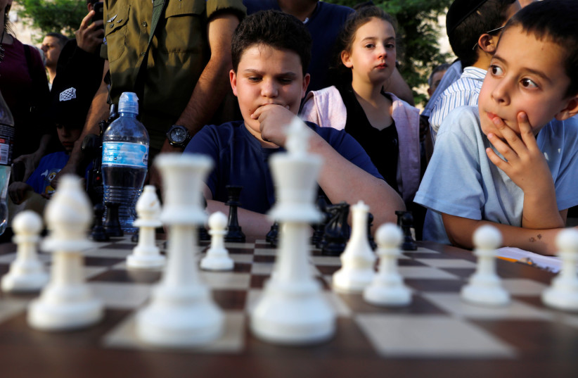 Israelis wait for their turn to play against former Indian chess world champion Viswanathan Anand and former Russian chess world champion Anatoly Karpov (both not pictured) as they play simultaneous matches against tens of Israeli players during an event marking Israel's 70th anniversary at Jerusale (photo credit: REUTERS/Ronen Zvulun)