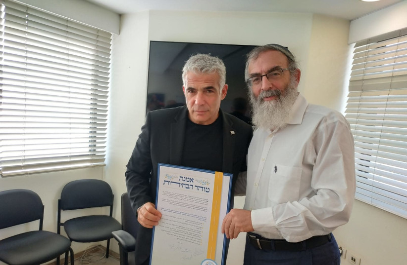 Yes Atid Party Leader Yair Lapid signs a vow of integrity and honesty ahead of the coming campaign with Rabbi David Stav, 2019. (photo credit: Courtesy)