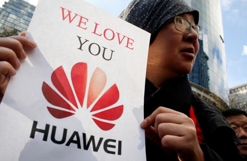 Lisa Duan, a visitor from China, holds a sign in support of Huawei outside of the B.C. Supreme Court bail hearing of Huawei CFO Meng Wanzhou, who is being held on an extradition warrant in Vancouver, British Columbia, Canada (photo credit: REUTERS/DAVID RYDER)
