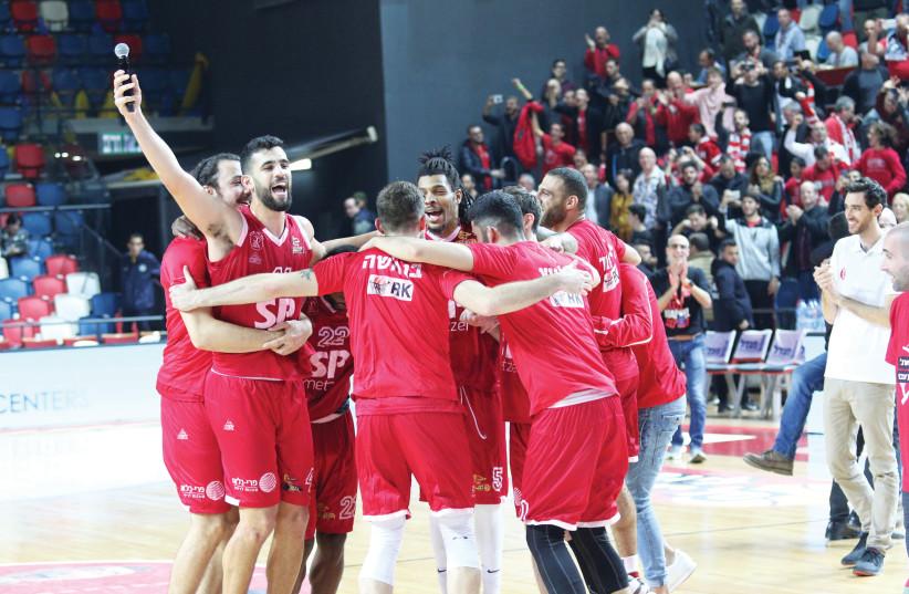 HAPOEL TEL AVIV players celebrate after the Reds beat city rival Maccabi Tel Aviv 104-94 in overtime in Basketball Super League action this week (photo credit: ADI AVISHAI)