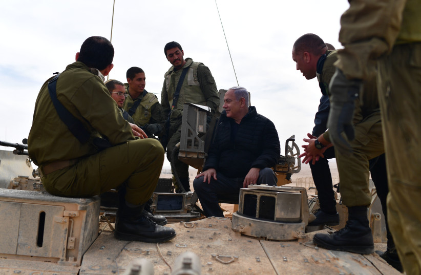 Benjamin Netanyahu speaks with soldiers on top of an IDF tank close to the Gaza Border January 23, 2019 (photo credit: GPO)