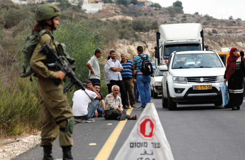 PALESTINIANS WAIT at an IDF checkpoint in the West Bank late last year. (photo credit: MOHAMAD TOROKMAN/REUTERS)