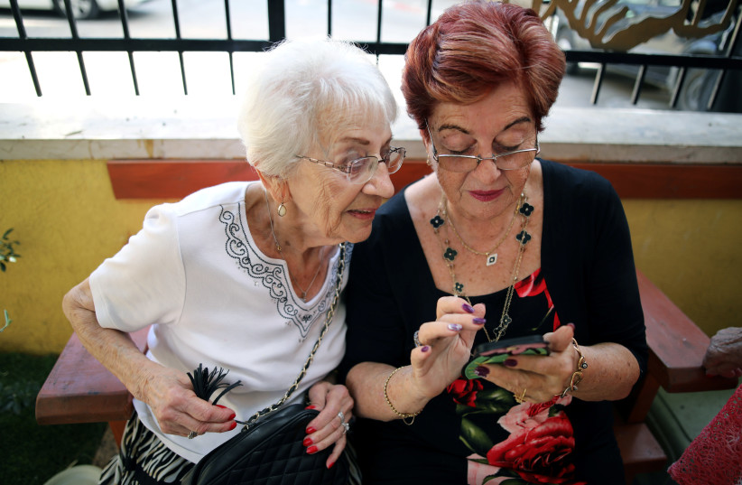 Holocaust survivors look at the mobile phone after they arrived to take part in the annual Holocaust survivors' beauty pageant in Haifa, Israel October 14, 2018 (photo credit: CORINNA KERN/REUTERS)