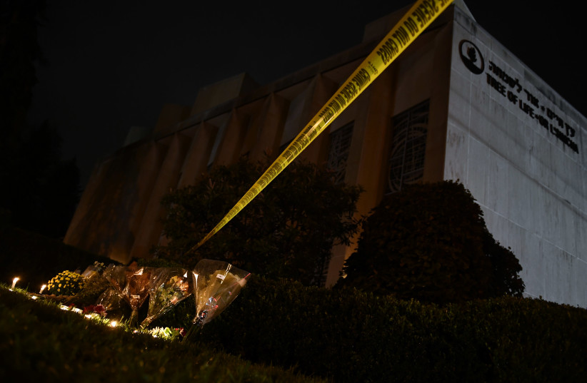 Flowers and candles are placed beneath a police cordon outside the Tree of Life Synagogue after a shooting there left 11 people dead in the Squirrel Hill neighborhood of Pittsburgh on October 27, 2018 (photo credit: BRENDAN SMIALOWSKI / AFP)