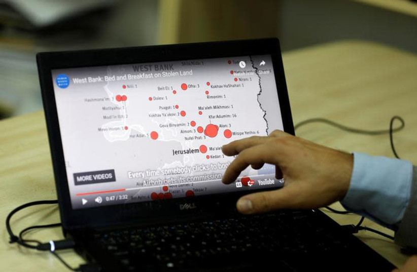 Omar Shakir, Israel and Palestine Director at Human Rights Watch, shows a map during an interview on home-renting company Airbnb's decision to remove listings in Israeli settlements, in Ramallah (photo credit: REUTERS/MOHAMAD TOROKMAN)