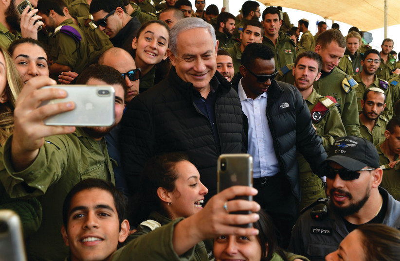 PRIME MINISTER Benjamin Netanyahu poses for selfies with soldiers at the Shizafon military base Wednesday (photo credit: KOBI GIDON / GPO)