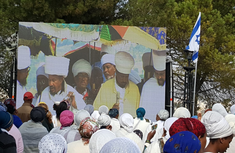 Leaders of the Jewish-Ethiopian community displayed on a large screen as they lead worshipers in the Sigd holiday prayers in Jerusalem, November 17, 2018. (photo credit: BEN BRESKY)