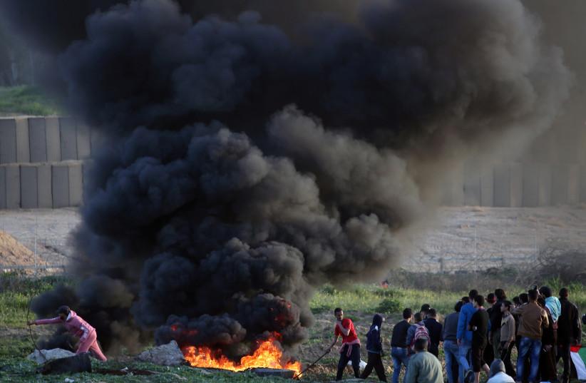 Palestinian demonstrators protest at the Israel-Gaza border fence, in the central Gaza Strip January 25, 2019 (photo credit: IBRAHEEM ABU MUSTAFA / REUTERS)