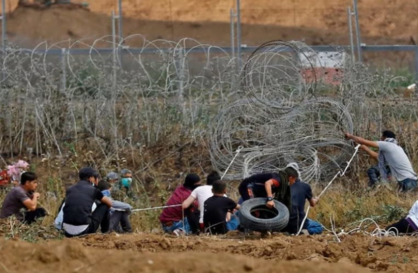 """Palestinian demonstrators disturb the Gaza-Israel border fence during the 44th weekly protest called the """"Great March Of Return"""" (photo credit: Courtesy)"""