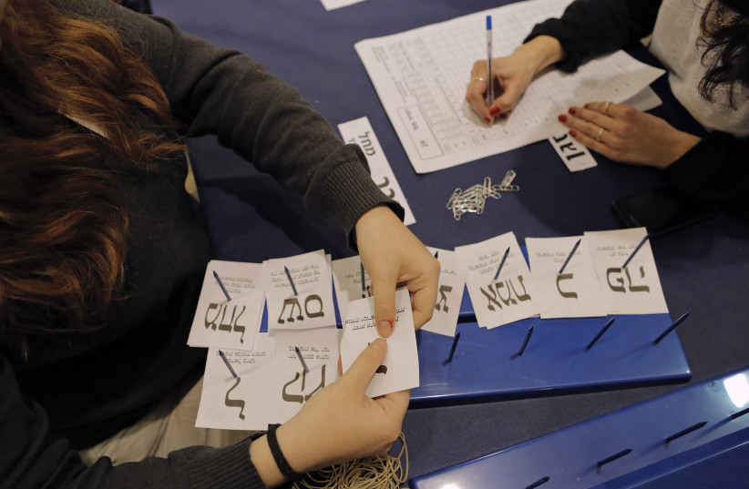 Israeli workers count ballots cast by Israeli soldiers and civil servants living overseas at the central elections committee building in the Knesset, the Israeli parliament, in Jerusalem March 18, 2015. (photo credit: AMMAR AWAD / REUTERS)